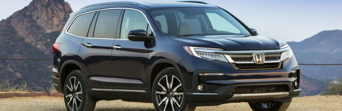 A front right quarter photo of the 2021 Honda Pilot parked near mountains.