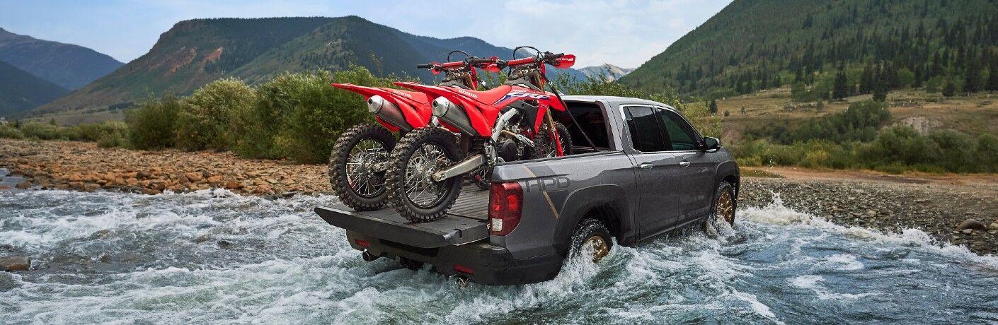 A rear right quarter photo of the 2021 Honda Ridgline hauling dirt bikes through a stream.