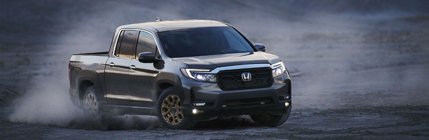 A front-right quarter photo of the 2021 Honda Ridgeline driving through dust.