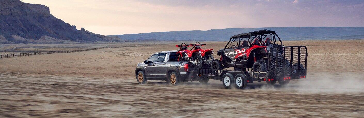 A photo of the 2021 Honda Ridgeline pulling a trailer.