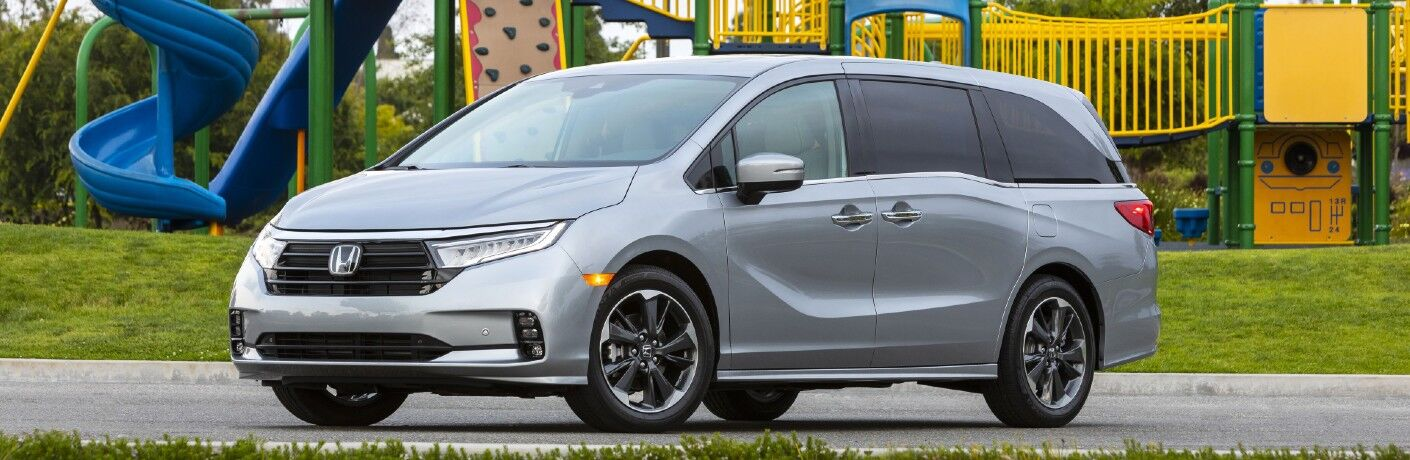 A lefit profile photo of the 2022 Honda Odyssey parked by a playground.