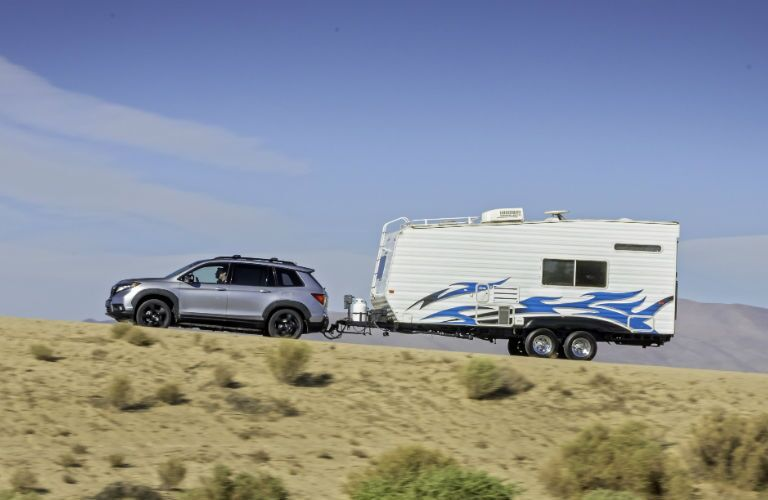 A photo of the 2021 Honda Passport towing a camper.