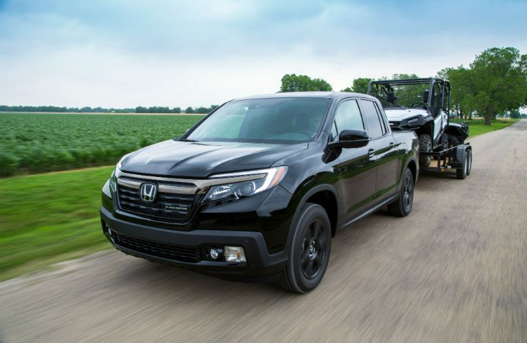 A front left quarter photo of the 2020 Honda Ridgeline pulling a trailer.