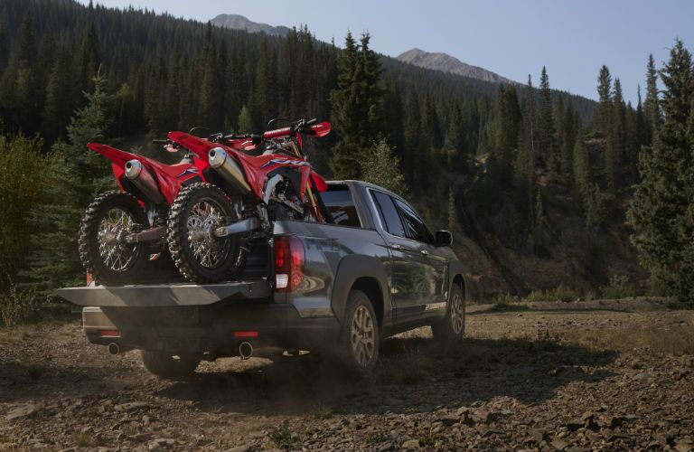 A rear photo of the 2021 Honda Ridgeline with dirt bikes in the cargo bed.