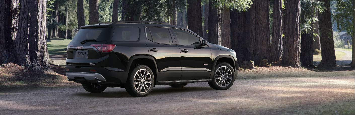A right profile view of a black 2018 GMC Acadia in the forrest