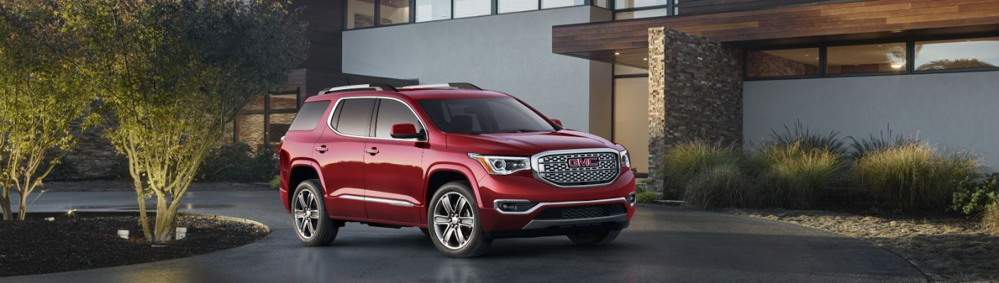 A photo of the Denali version of the 2018 GMC Acadia parked in a driveway.