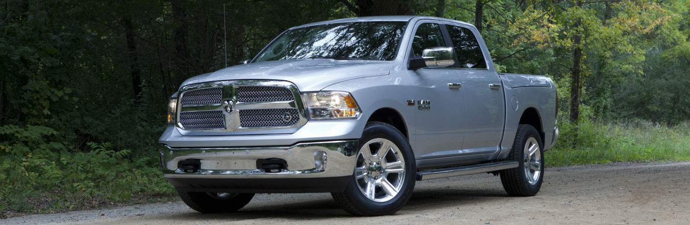 A left front quarter view of a silver 2018 Ram 1500 pickup truck in the woods