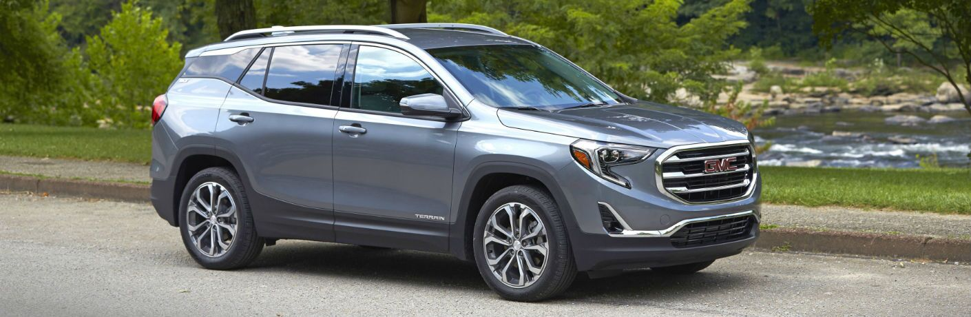 A right profile photo of the 2018 GMC Terrain parked in front of a river