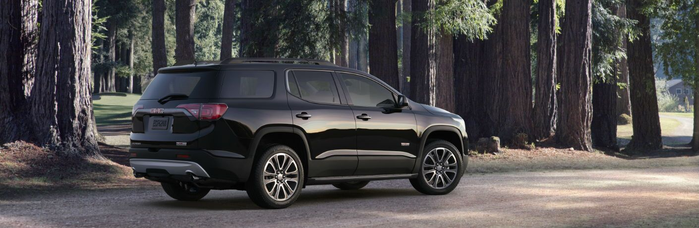 A right profile photo of the 2019 GMC Acadia parked in the woods.