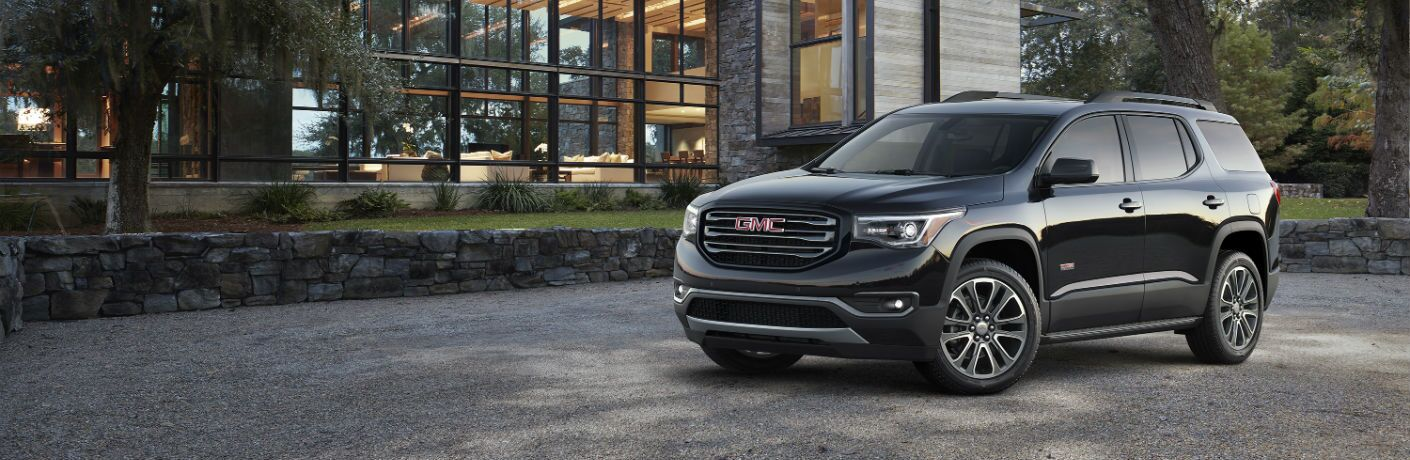 A left profile photo of the 2019 GMC Acadia parked in front of a house.