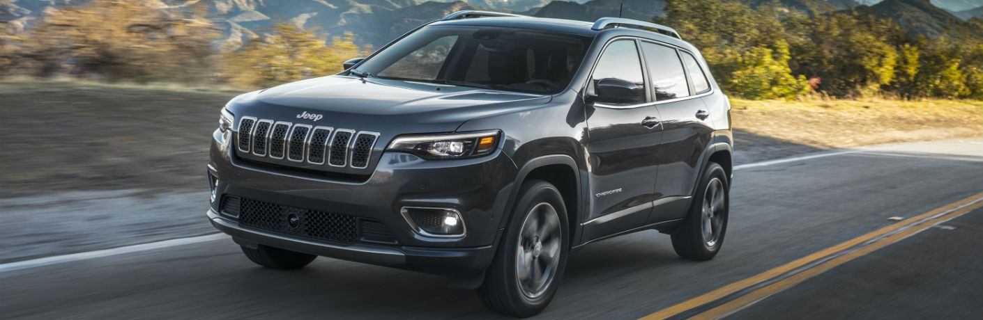 A front left quarter photo of the 2019 Jeep Cherokee in motion on a desert road.