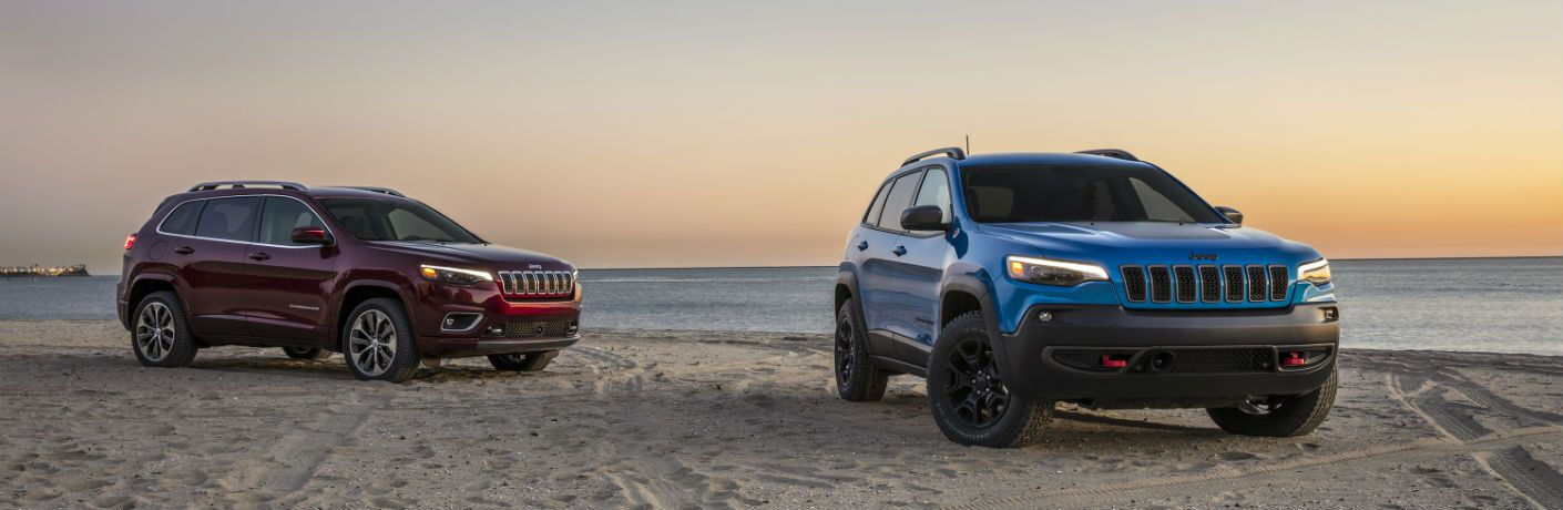 Two versions of the 2019 Jeep Cherokee models parked on a beach.