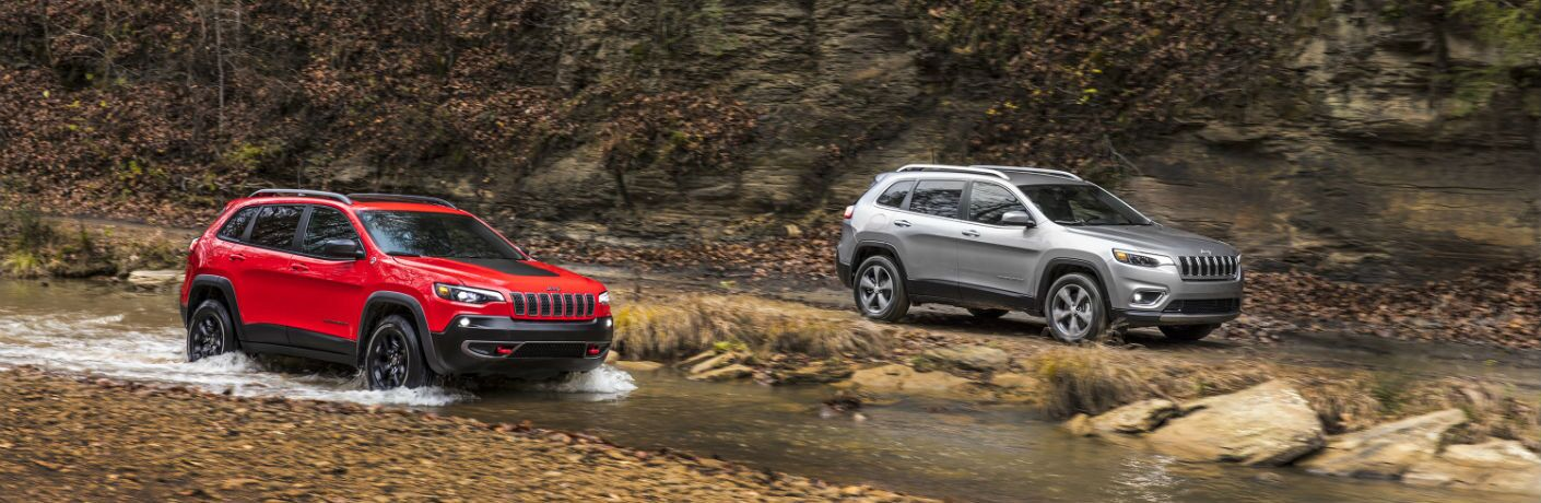 A photo of two versions of the 2019 Jeep Cherokee driving over trails in the woods.