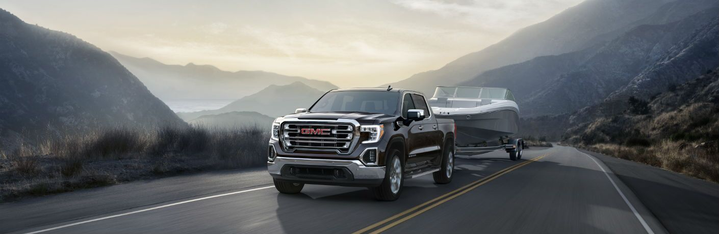 A photo of the 2019 GMC Sierra pulling a boat on a trailer.