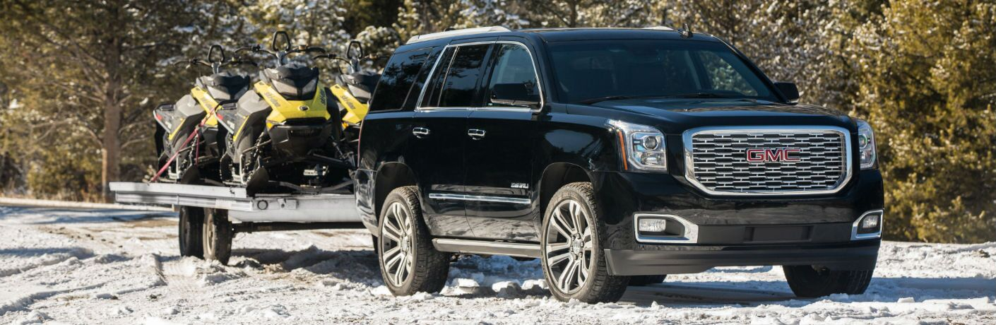 A front-right quarter photo of the 2019 GMC Yukon Denali pulling a trailer.