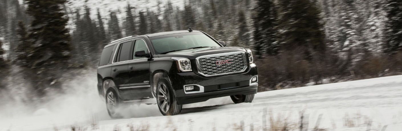 A right quarter profile photo of the 2019 GMC Yukon on a snow-covered road.