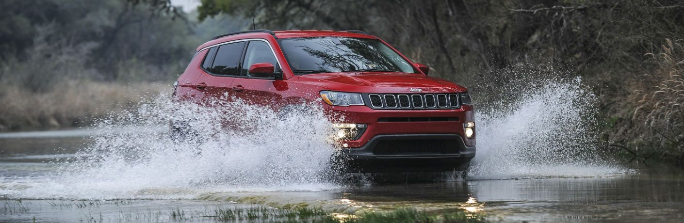A photo of a 2019 Jeep Compass crossing a river.