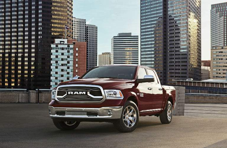 A front left view of a dark red 2018 Ram 1500 in front of a city skyline.