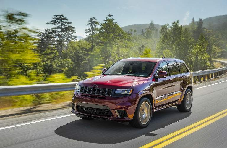 A front left quarter image of the 2018 Jeep Grand Cherokee driving down the road