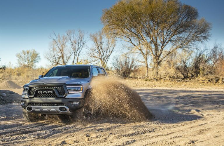 A photo of the 2019 Ram 1500 splashing through a puddle of mud.