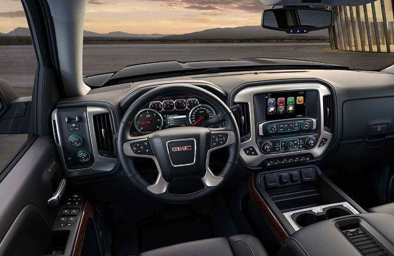 2017 GMC Sierra interior showing gauge cluster and infotainment system. These features are available with the selected inventory for the Billion Auto Group sale