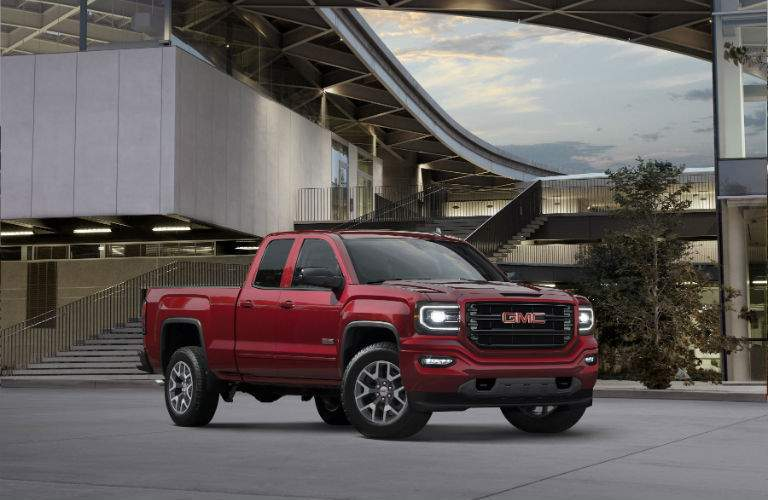 A front right quarter view of the 2018 GMC Sierra in front of a building