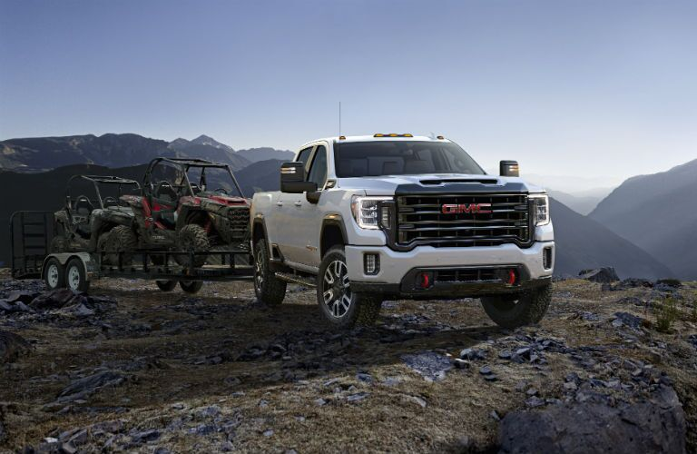 A front right quarter photo of the 2020 GMC Sierra 2500HD pulling a trailer of ATVs.