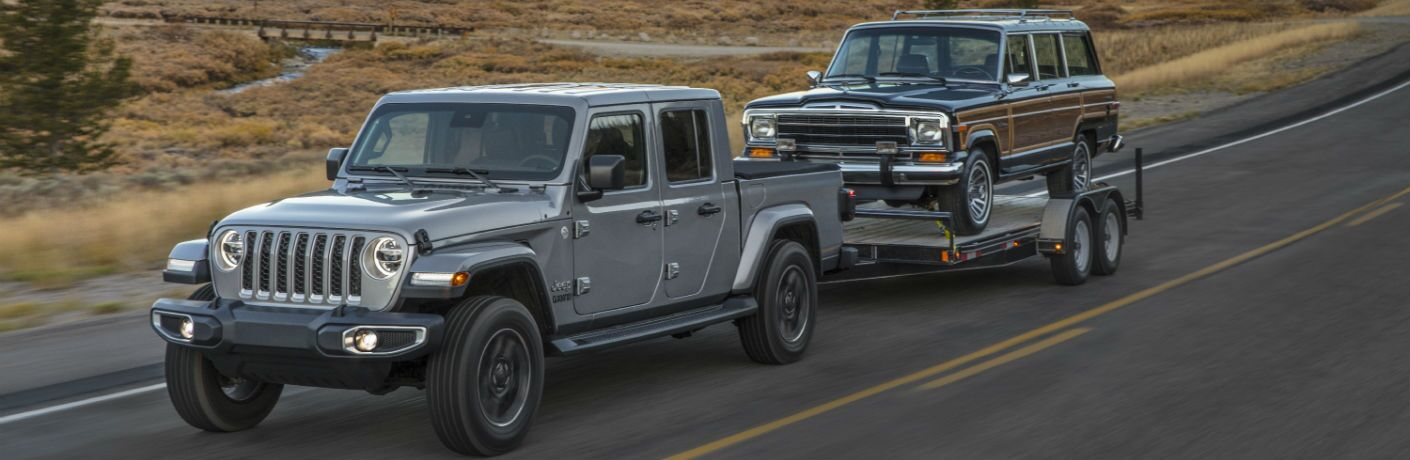 A photo of the 2020 Jeep Gladiator pulling a vehicle on a trailer on the road.