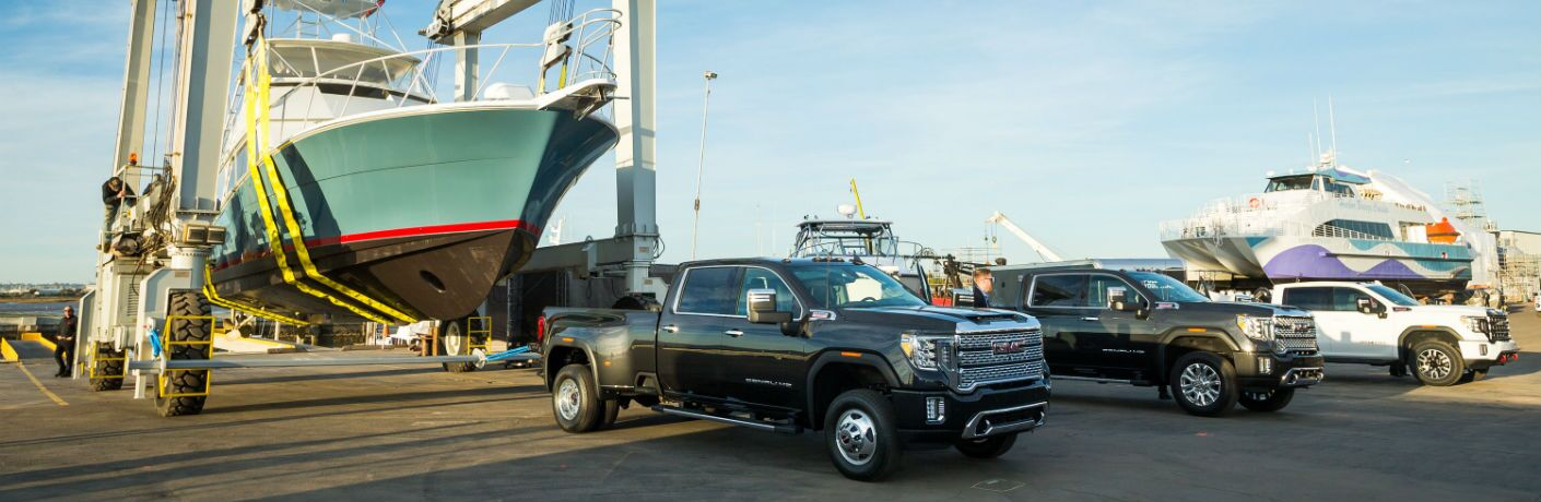 A photo of three versions of the 2020 GMC Sierra 2500HD lined up at a ship yard.