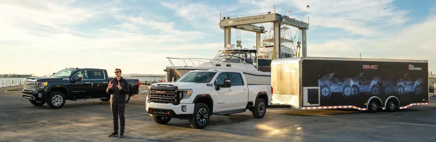 A photo of a man speaking in front of a pair of 2020 GMC Sierra 2500HD models at a ship yard.