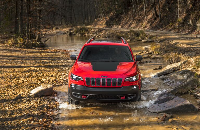 A photo of a 2019 Jeep Cherokee going through a mud hole.