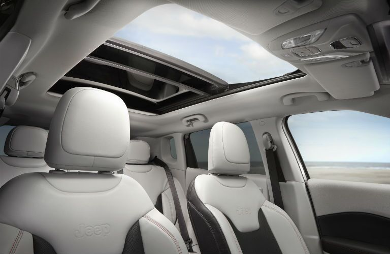 A photo of the front seats and sunroof in the 2019 Jeep Compass.