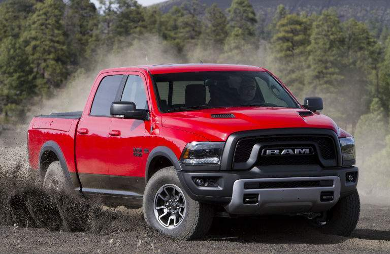 A red 2018 Ram 1500 kicking up dirt in an empty field in the woods