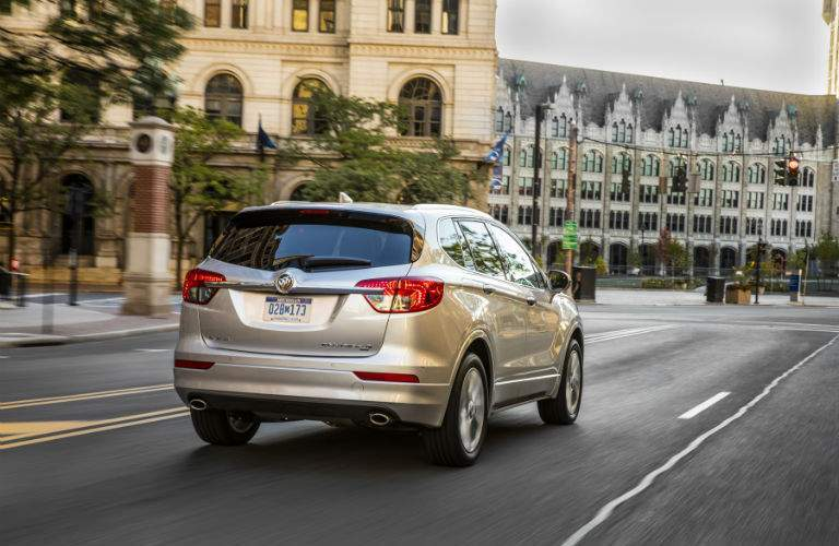 A rear photo of the 2018 Buick Envision driving through a city
