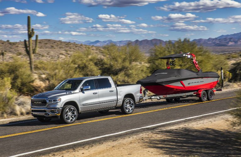 A photo of the 2019 Ram 1500 pulling a boat on the road.