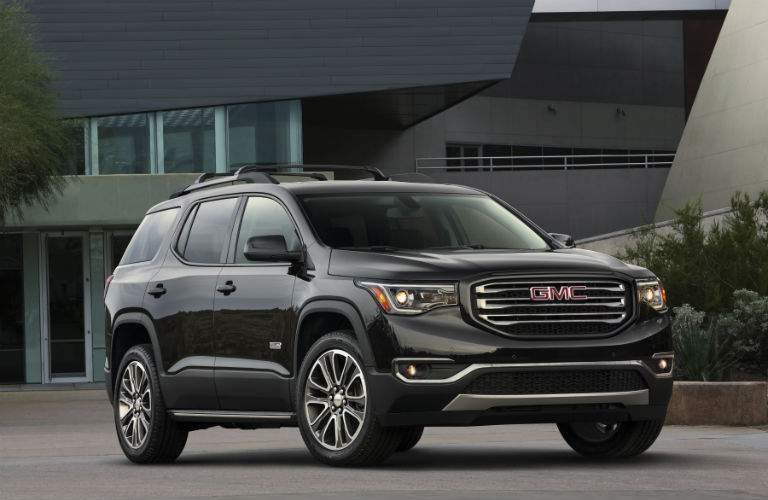 A photo of the 2018 GMC Acadia in front of a performing arts center showing one of several unique grille designs