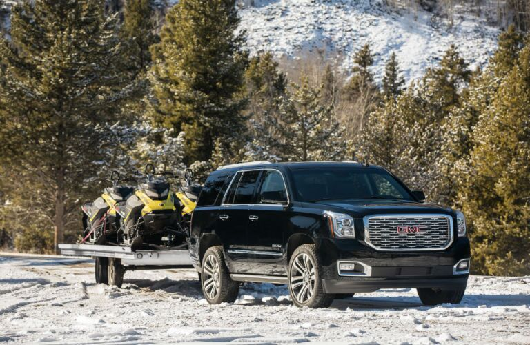 A photo of the 2019 Yukon towing snowmobiles.