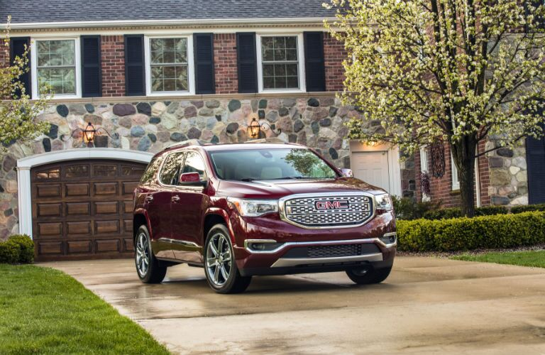 A front right profile photo of the 2018 GMC Acadia parked in front of a home.