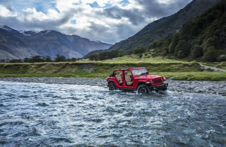 A photo of a 2018 Jeep Wrangler fording a river in the mountains