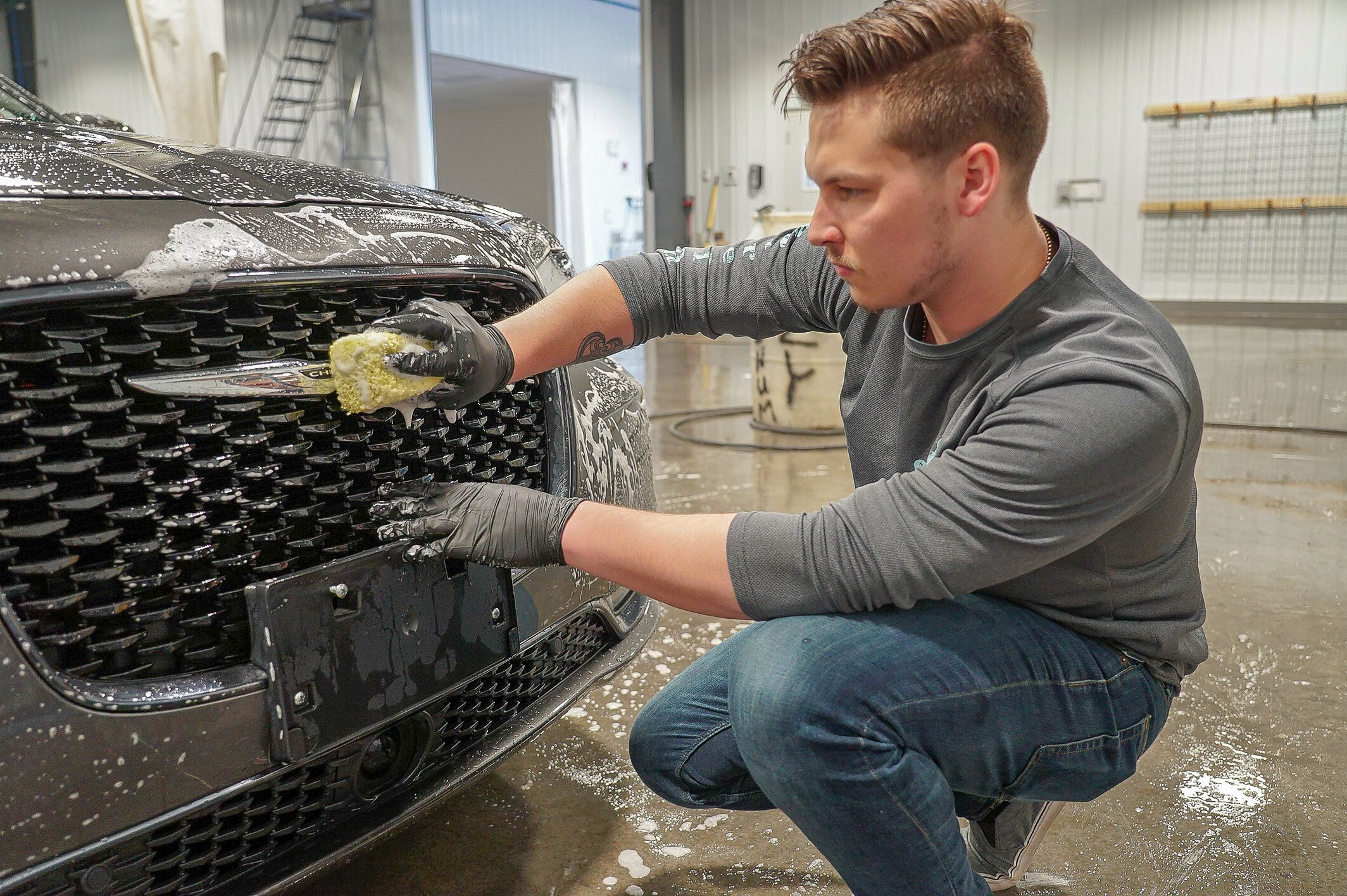A photo of a detail shop employee cleaning a new car for display on the lot.
