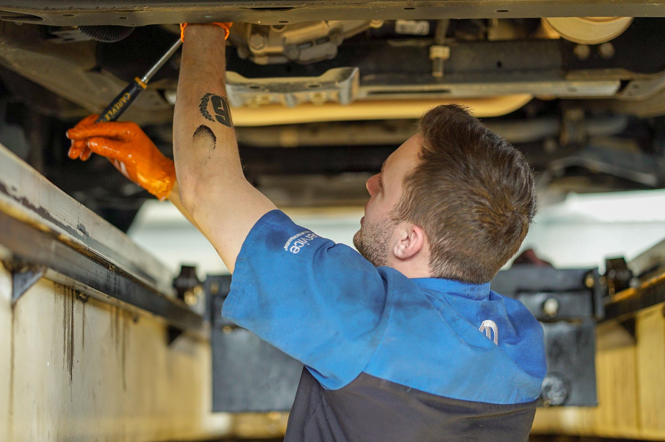 A photo of an oil change technician at work.