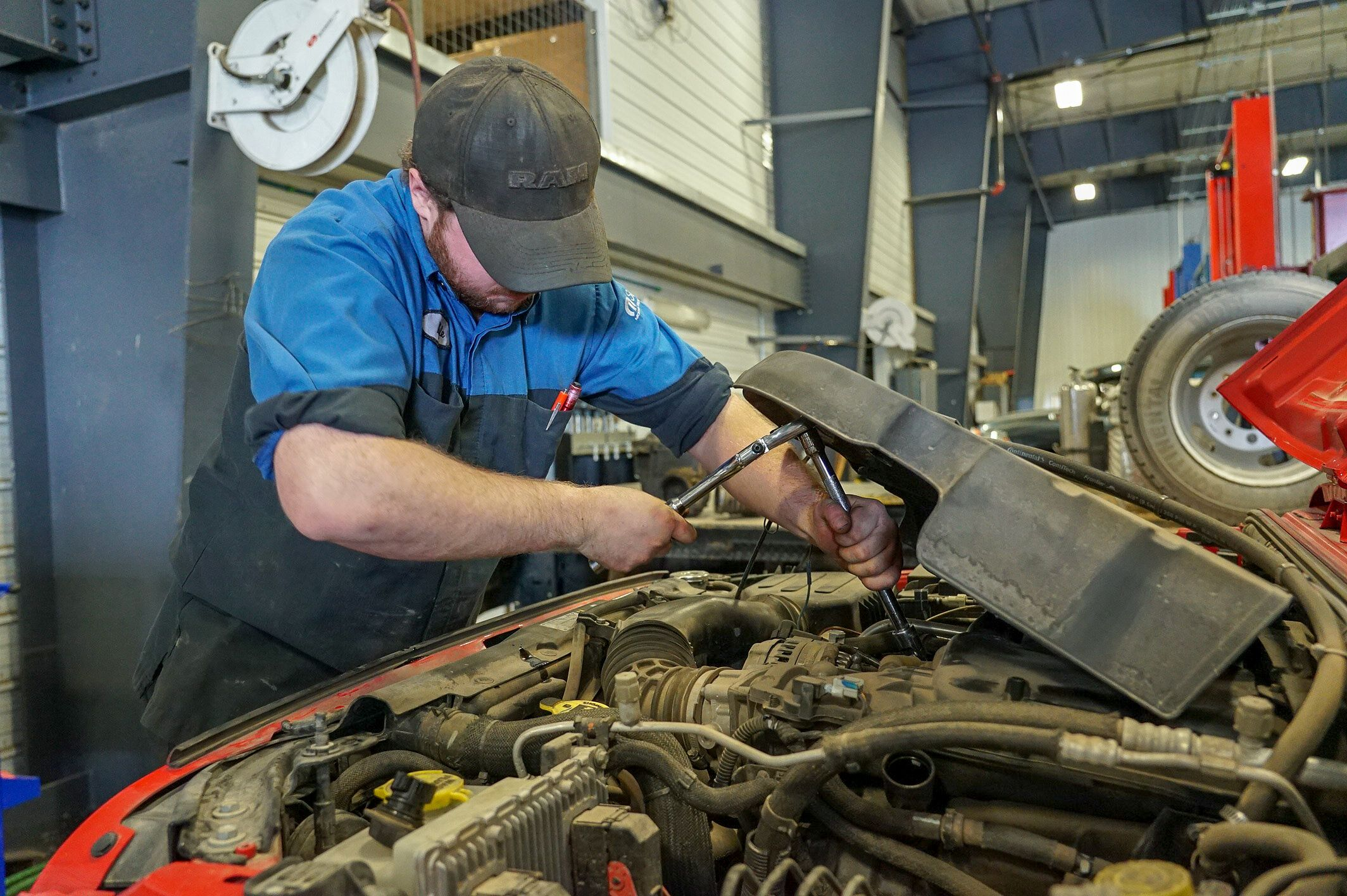 A photo of a service technician working on a vehicle.