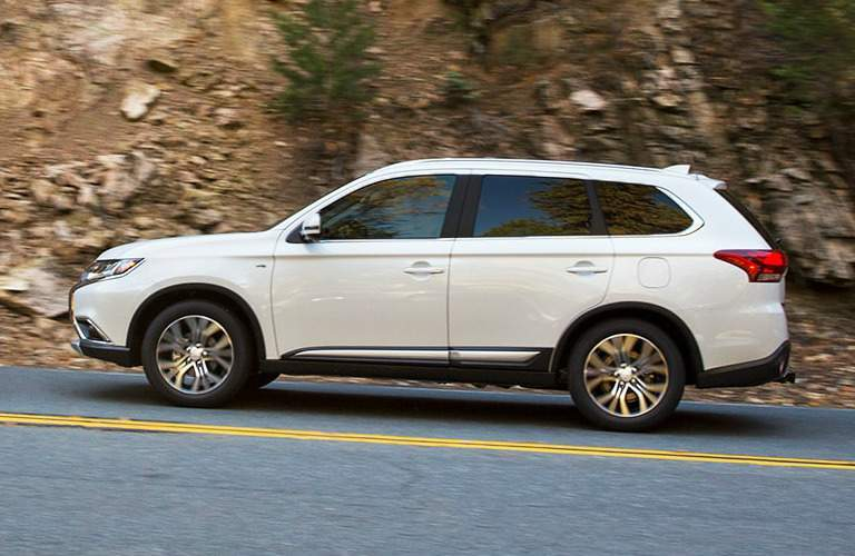 side view of 2018 Mitsubishi Outlander driving up hill