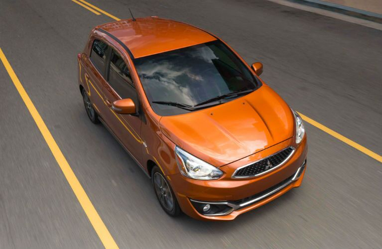 2018 Mitsubishi Mirage in orange driving down a road