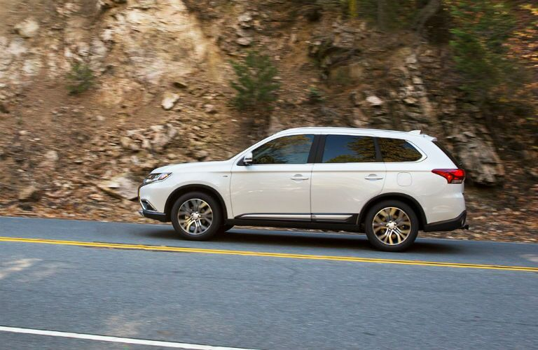2018 Mitsubishi Outlander driving along a wooded, dirt cliff