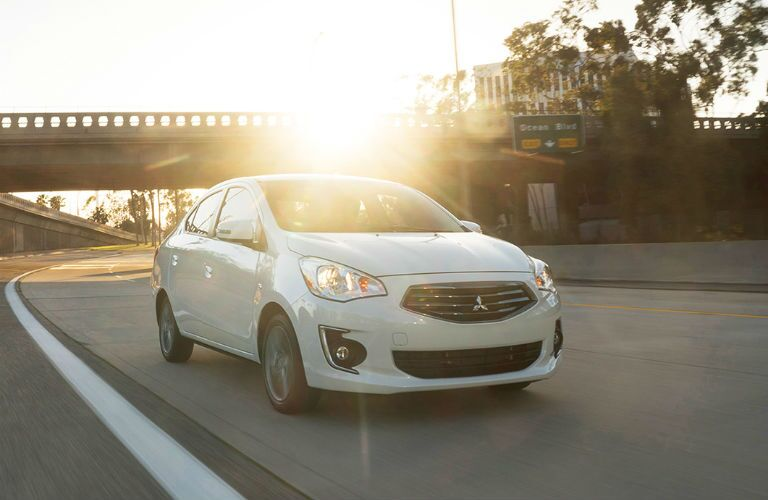 2019 Mitsubishi Mirage G4 driving past a bridge with the sun setting