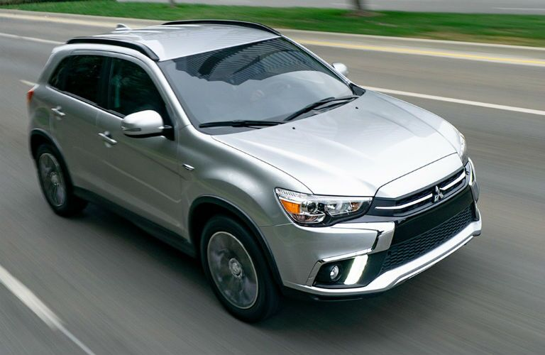 Overhead view of silver 2019 Mitsubishi Outlander Sport driving on empty highway road