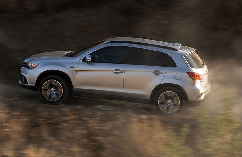 Profile view of silver 2019 Outlander Sport driving up hill