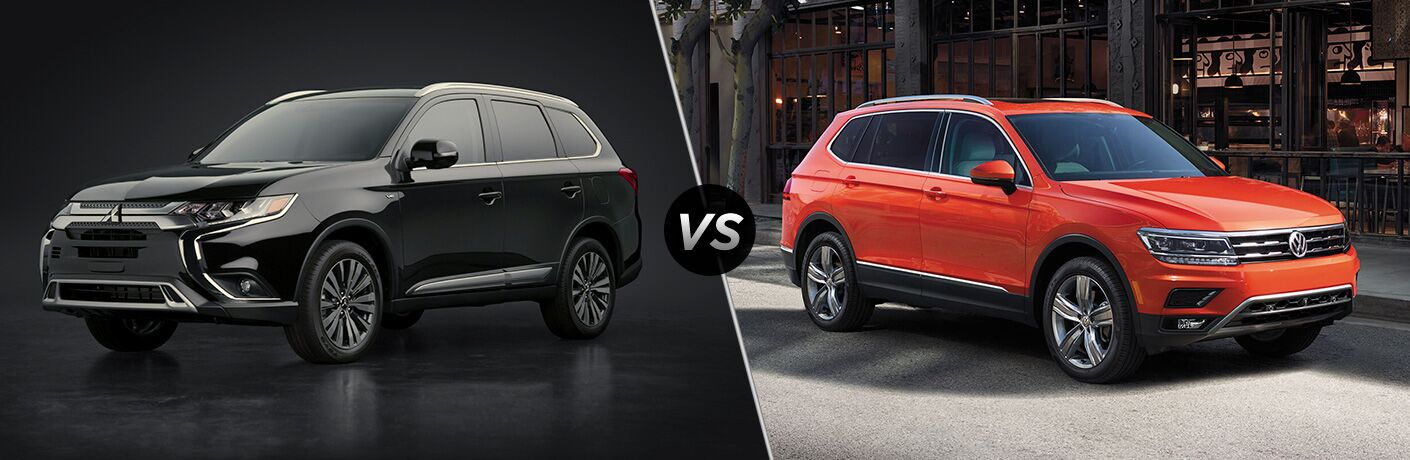 Front driver angle of a black 2020 Mitsubishi Outlander on left VS front passenger angle of an orange 2020 Volkswagen Tiguan on right