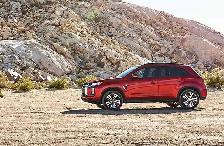 red mitsubishi outlander sport parked by a rock formation
